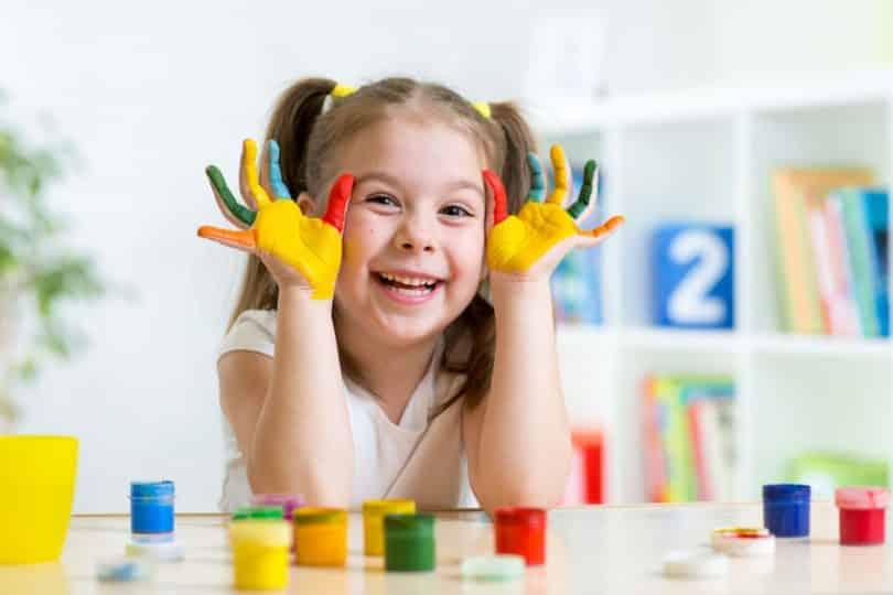 Criança com mãos pintadas de tinta colorida sorrindo