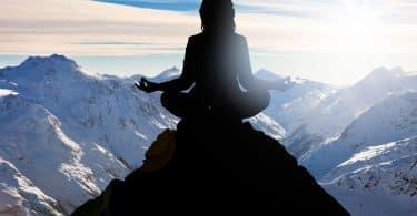 Mulher medita em pico de montanha.
