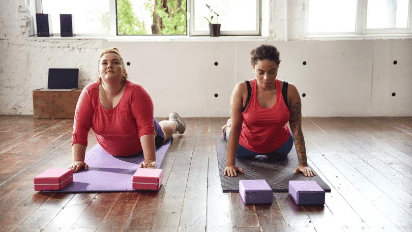 Duas mulheres em uma sala praticando yoga no chão