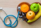 Imagem de frutas em um recipiente em formato de coração. Ao lado, um estetoscópio.