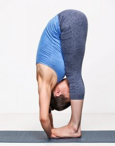 Sporty fit woman practices yoga asana Padahastasana - standing forward bend with hand under feet