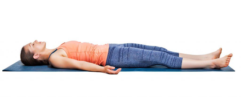 Beautiful sporty fit yogini woman relaxes in yoga asana Savasana - corpse pose in studio
