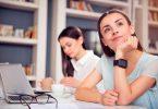 Mulher sentada em uma mesa com expressão pensativa em ambiente de trabalho.