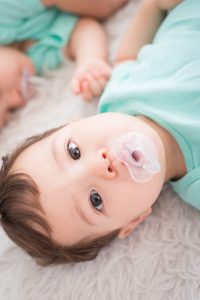 Cute Newborn baby twins smile to you with pacifier. Closeup portrait caucasian child