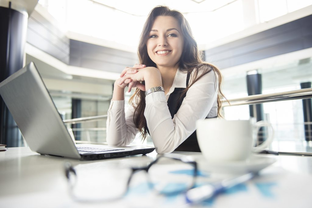 Smiling young business woman working for a laptop in a modern office.