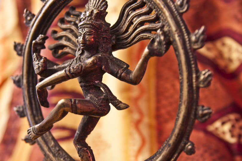 A close-up of a bronze/brass antique statue depicting the Indian god Shiva.