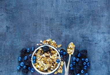 Tasty breakfast table with granola in vintage bowl and dark berries on grunge background. Copy space top view. Organic healthy food and diet concept.