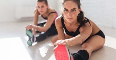 Group of fit women working stretching leg muscles and back to warm up at gym fitness, sport, training and lifestyle concept ** Note: Shallow depth of field