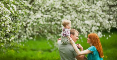 Happy family having fun outdoors in spring garden. Father mother and child. Family concept