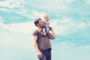 Lifestyle atmospheric portrait happy father and son having fun outdoors against blue sky with clouds soft vintage pastel colors