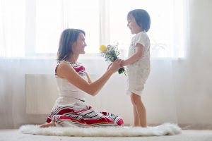 Mother and her child embracing with tenderness and care child giving mother flowers. Mother day concept happiness and love