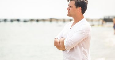Portrait of handsome young man looking on the horizon at sea