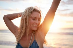 Closeup portrait of smiling young caucasian woman at the beach. Cheerful young woman enjoying a day on the sea shore at sunset.