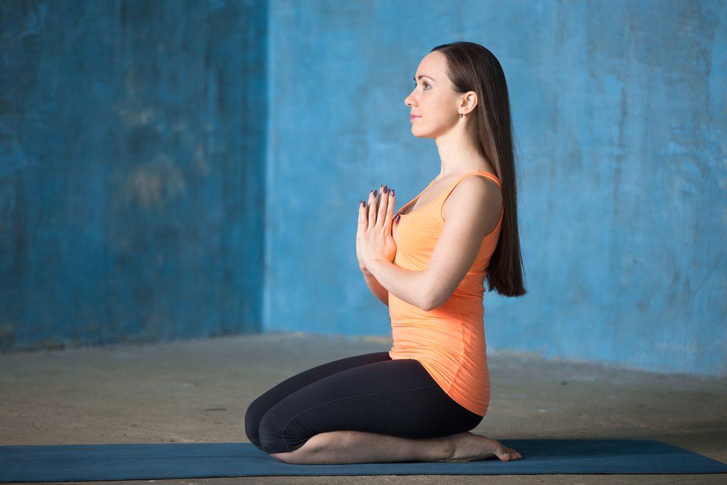Mulher sentada no chão com as mãos unidas