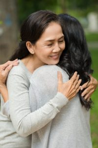 Mature woman tightly hugging her best friend