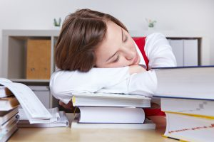 Tired woman sleeping on books after studying for exams
