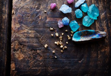 Treasure hunting. Mining for gems. Gold and gems on rough wooden surface.