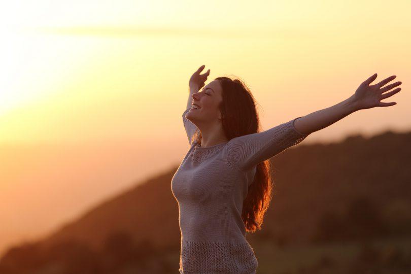 Mulher de braços aberto e sorrindo em campo aberto com a luz do pôr do sol