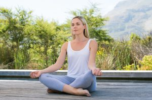 Woman practicing yoga and meditating outdoors. Mature woman relaxing with lotus yoga position in the morning. Relaxed woman doing yoga and meditation with closed eyes.