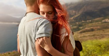 Close up shot of young woman hugging her boyfriend. Young couple in love embracing outdoors.