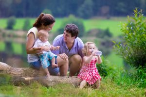 Family on summer hike. Young parents with kids hiking next to a lake. Mother father and two children having picnic outdoors. Active trekking with baby and toddler. Beautiful nature of Germany.
