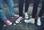 Young rebel teenagers wearing casual sneakers walking on dirty concrete. Canvas shoes and sneakers on female adults