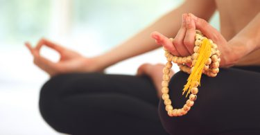Young beautiful woman meditating in lotus pose. ** Note: Shallow depth of field