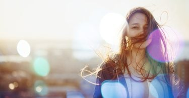 Young Woman Standing in Sunset Light Looking at Camera. Hair Fluttering in the Windi. Selective Focus Bokeh Lights.