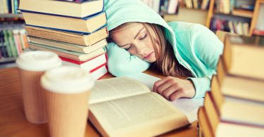 people, education, session, exams and school concept - tired student girl or young woman with books and coffee sleeping in library