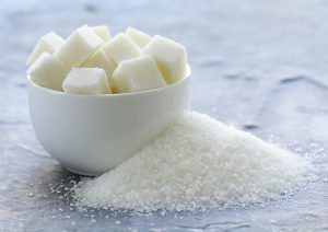 white granulated sugar and refined sugar on a gray background