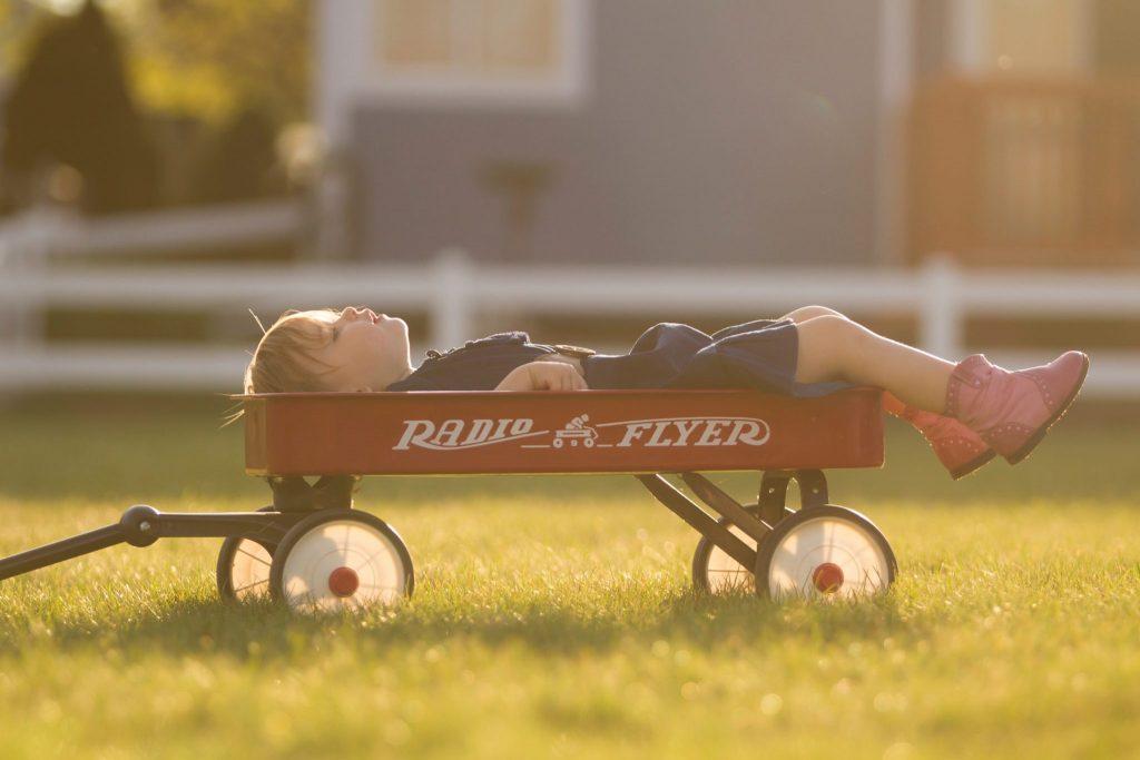 Menino deitado em cima de um carrinho de mão.