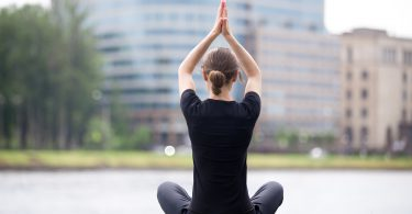 Young woman sitting cross legged on riverbank in front of blue glass modern office building practicing yoga Easy Pose Sukhasana posture for meditation pranayama breathing full length back view