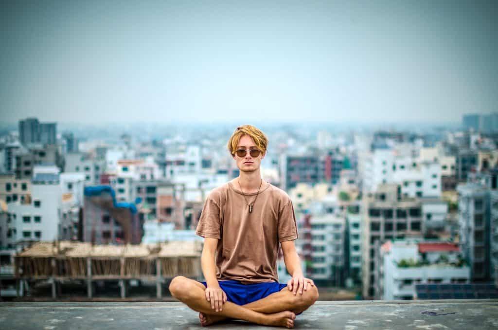 Homem sentado no topo de um prédio e atrás a cidade