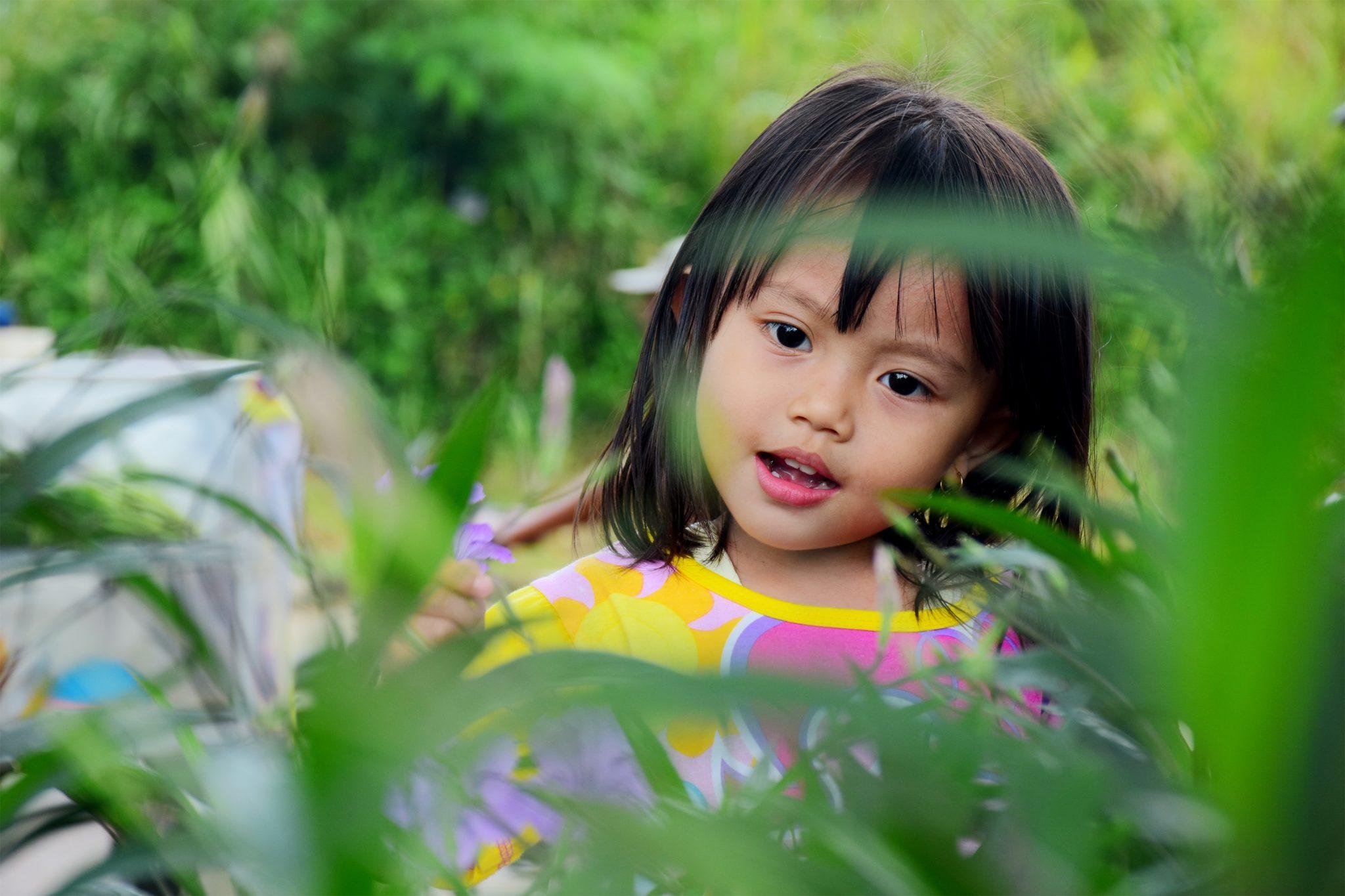 Menina de cabelos pretos e lisos entre folhas segurando uma florzinha roxa.