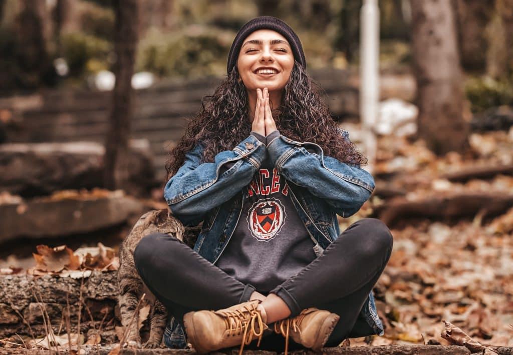 Mulher sentada em folhas secas no chão sorrindo e de olhos fechados mantendo suas mãos juntas