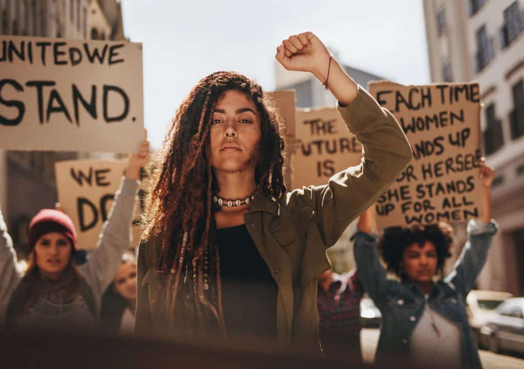 Mulher em protesto segurando cartazes