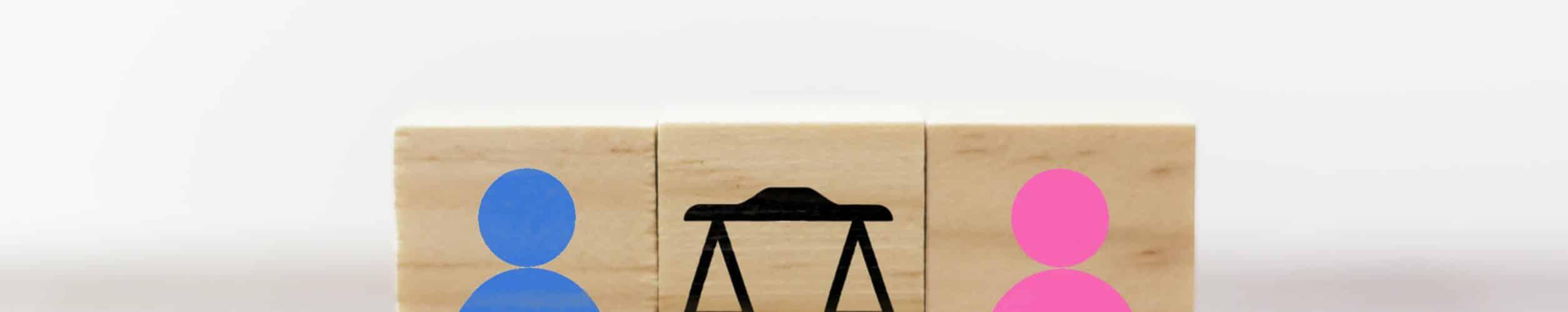 Cubos de madeira representando um homem, uma mulher e uma balança entre eles.