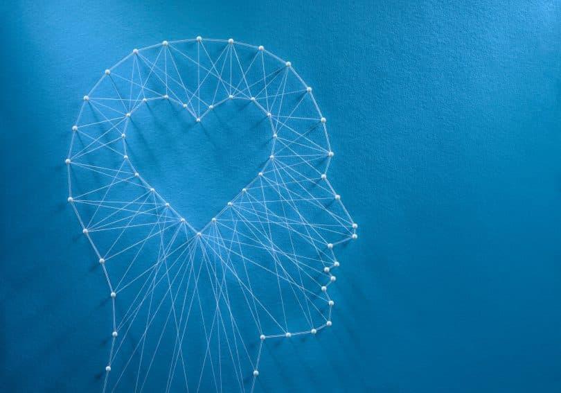 Rede de alfinetes e fios em forma de coração dentro de uma cabeça humana.