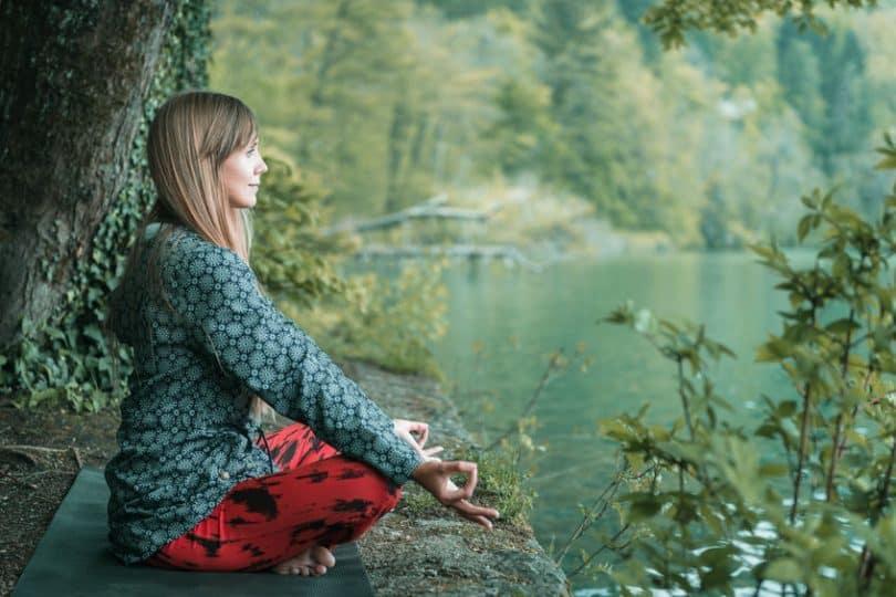 Mulher sentada meditando com lago ao fundo