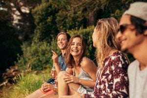 Portrait of cheerful young friends hanging out with beers. Group of friends sitting outdoors and having fun.