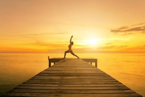 Yoga pose - Woman silhouette practicing yoga Warrior pose on sea bridge at sunset.Yoga near beach.