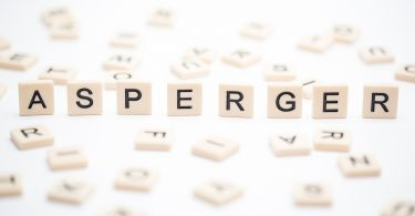 Asperger spelled out in plastic letter pieces with others scattered around on white background