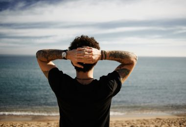 Caucasian boy on beach standing in sand with hands behind head and looking at ocean enjoying sun and summer travel holidays vacation getaway in Spain. Boy with tattoos in black t-shirt and jeans relaxing under blue sky.