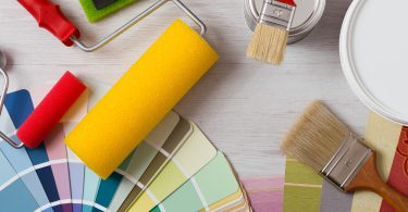 Painter and decorator work table with house project color swatches painting roller and paint brushes top view