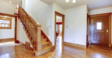 Empty house interior. Entrance hallway with new shiny hardwood floor and staircase