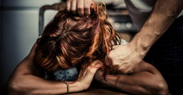 Man is Physically Abusing His Girlfriend who is sitting at a table in the kitchen