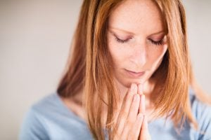 Closeup portrait of a praying young woman with closed eyes. ** Note: Shallow depth of field