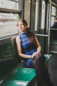 Pensive pretty girl sitting inside subway train