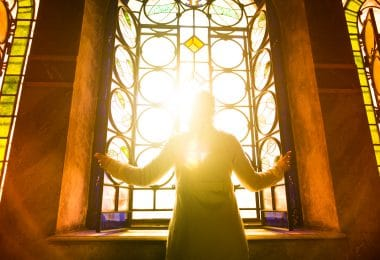 Religious christian woman looking trough the stained glass church window light.Woman praying to god at St. Alexander Nevsky Cathedral.Christianity.Strong religion,faith and spiritual.Enlightenment