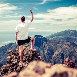 Trail runner man and success in mountains. Motivation and inspiration on mountains peak. Running sports fitness and healthy lifestyle outdoors in summer nature